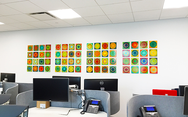Collection of small geometric paintings hanging in an office space