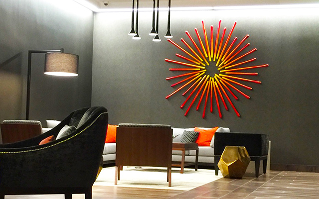 A sunburst inspired 3d art piece, hanging in a hotel lobby