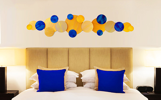 Blue and yellow abstract wall hanging, shown over bed in hotel room