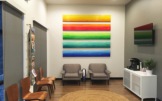 Rainbow painted wood wall sculpture in a healthcare lobby