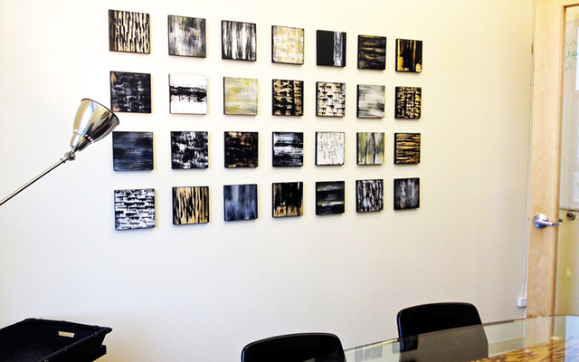 Original black and white paintings on wood blocks, displayed in an office meeting room