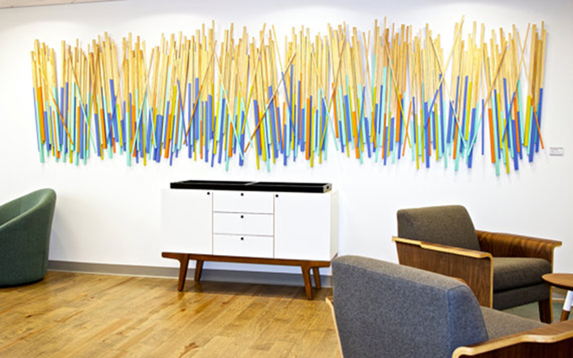 Wood sticks, dipped in pops of color and hanging in healthcare waiting room